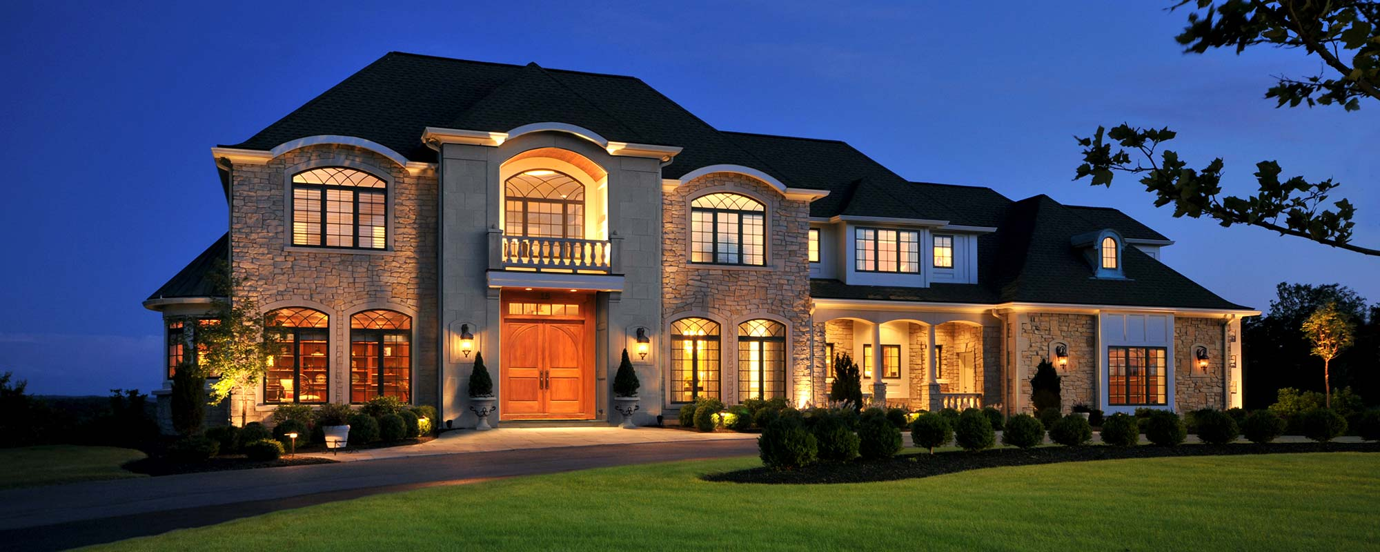 Ketmar home. Front view of a large house lit with many interior and exterior lights